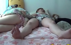 Oriental teens piddle on bed